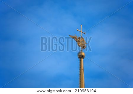 The angel on the spire of the Peter and Paul Cathedral in St. Petersburg. The gilded spire of the Church of Saints Peter and Paul in the Peter and Paul fortress. The figure of a Golden guardian angel and cross in the snow on blue sky background.