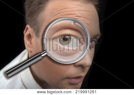 portrait of a man looking in a magnifying glass closeup