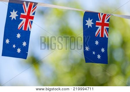 Australian flags on bunting isolated against out of focus background. Australia day celebrations.