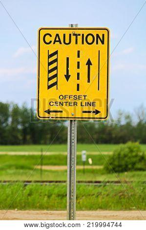 A caution offset center line road sign.
