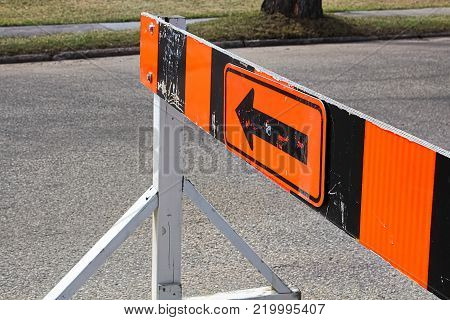 A road closer with arrow construction barrier.