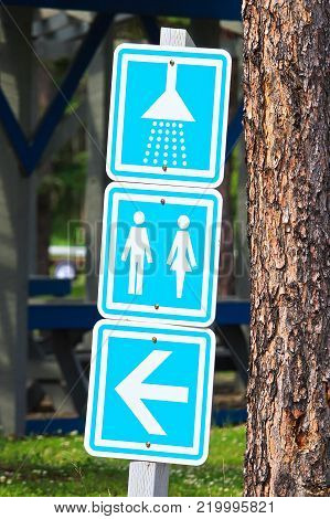 A showers and washroom directions sign at a campground.