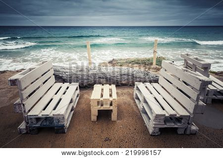 Standard white wooden furniture made of cargo pallets, cheap seaside terrace on Porto Santo, Madeira archipelago, Portugal