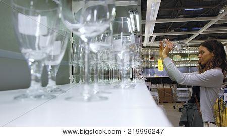 Caucasian girl chooses glasses at the hardware store, 4K.