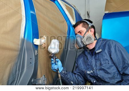 Profesional car painting in a paint booth.