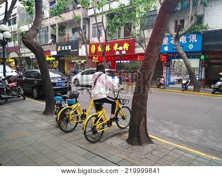 ZHONGSHAN,GUANGDONG,China-November 24,2017:girl ready to ride a shared bike.Bicycle-sharing is very popular in China.