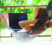 Young woman lying in a hammock with laptop poster