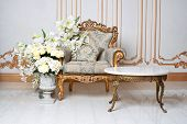 Luxurious vintage interior in the aristocratic style with elegant armchair and flowers. Retro, classics poster