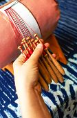 Making bobbin lace in traditional way. Detail on hands holding wooden bobbins with wound thread. Pillow lace. poster