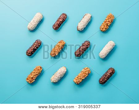 Set Of Different Homemade Eclairs On Blue Background. Top View Of Delicious Healthy Profitroles With