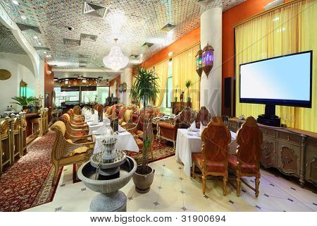 eastern interior of luxury restaurant, potted palms and fountain