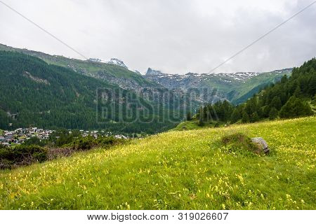 Idyllic Landscape In The Alps With Fresh Green Meadows, Mountain Tops In The Background, Zermatt, Sw