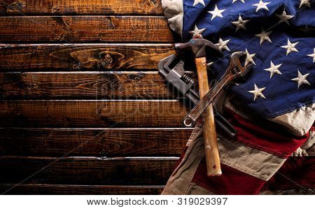 Old and worn work tools on large American flag - Labor day background