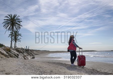 Young Attractive Traveler With A Red Suitcase Standing On A Deserted Beach On The Background Of The