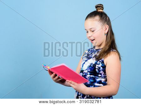 Keeping Secrets Here. Keeping Her Secrets In Diary. Child Cute Girl Hold Notepad Or Diary Blue Backg