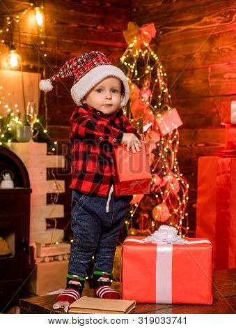 Open Gift. Lovely Baby Enjoy Christmas. Santa Boy Little Child Celebrate Christmas At Home. Childhoo