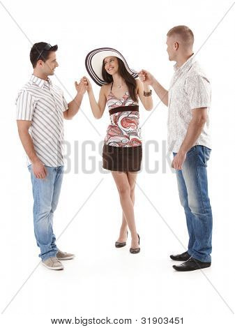 Pretty woman in mini skirt and straw hat standing with two men in summer shirt, holding hand, smiling, cutout on white.