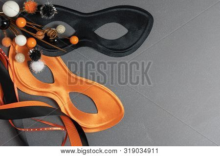 Trick Or Treat Background With An Orange And A Black Mask, Ribbons And A Novelty Ball Decoration Wit