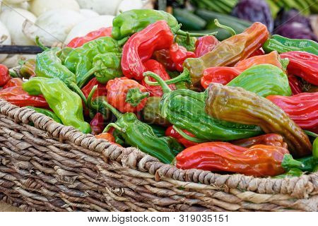Woven Basket Filled With Colorful Red And Green Wrinkly Textured Italian Long Hot Peppers At The Far
