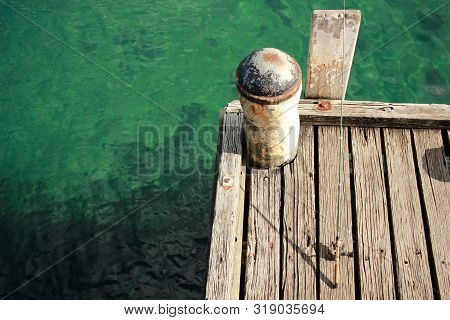 Fishing Equipment Cast Into The Ocean On An Old Timber Jetty Waiting For Fish To Bite, Coastal Victo