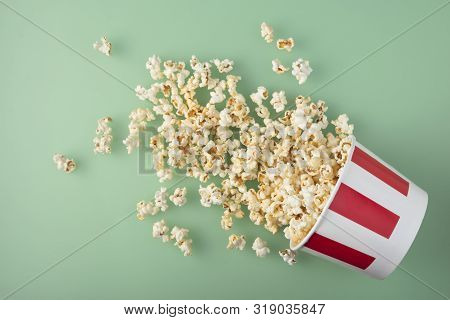 Overturned Striped Paper Cup With Delicious Fresh Popcorn On Green Background. The Concept Of Entert