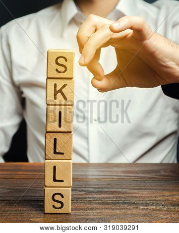 Businessman Knocks Down Wooden Blocks With The Word Skills. The Concept Of The Loss Of Skills. Suppr