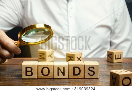 Wooden Blocks With The Word Bonds And Businessman. A Bond Is A Security That Indicates That The Inve