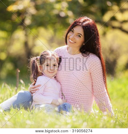 Happy mother and daughter in the autumn park. Beauty nature scene with family outdoor lifestyle. Happy family resting together on green grass, having fun outdoor. Happiness and harmony in family life