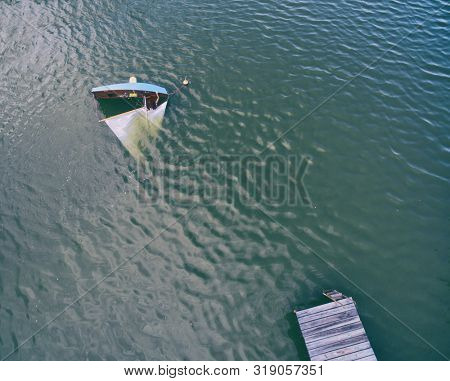 Aerial view of an overturned sailboat at the lake. Woman is trying to prevent the boat from drowning disaster