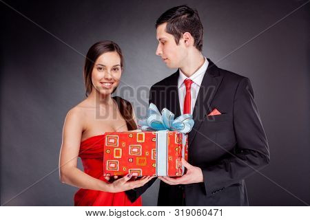 elegant couple in evening wear with a gift box
