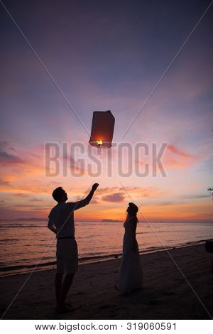 couple launches a flashlight at sunset