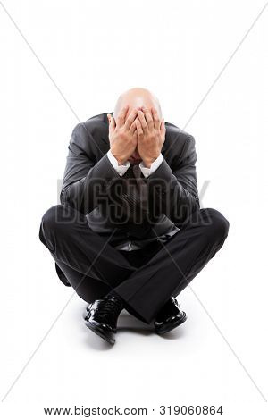 Business problems and failure at work concept - unhappy crying tired or stressed businessman sitting floor in depression hand hiding face white isolated
