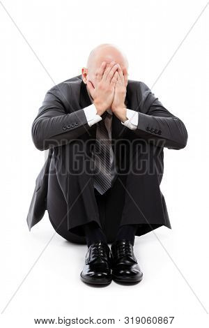 Business problems and failure at work concept - unhappy crying tired or stressed businessman in depression sitting down floor hand hiding face white isolated