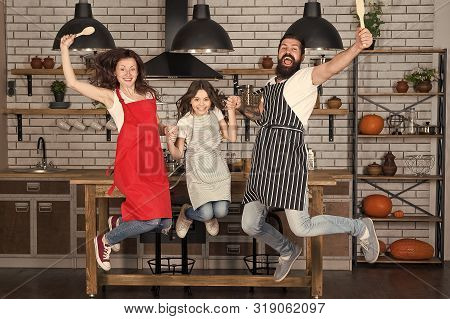 Cooking With Child Might Be Fun. Having Fun In Kitchen. Family Mom Dad And Little Daughter Wear Apro