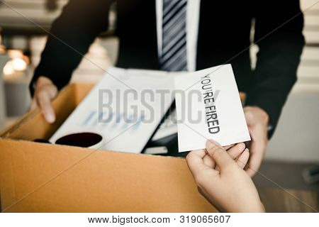 Female manager submits a resignation letter or envelope to the male employee at the office. poster