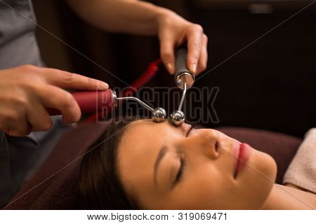 poster of people, beauty, cosmetology and technology concept - close up of beautiful young woman having needle free mesotherapy or hydradermie facial treatment by microcurrent firming device in spa