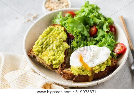 Delicious Rye Bread Toast With Avocado And Poached Egg Served With Kale And Tomato Salad. Healthy Ve
