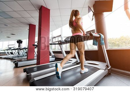 Slim Beautiful Sporty Girl Running At The Treadmill In The Gym Against Sunset. Concept Of Cardio Exe