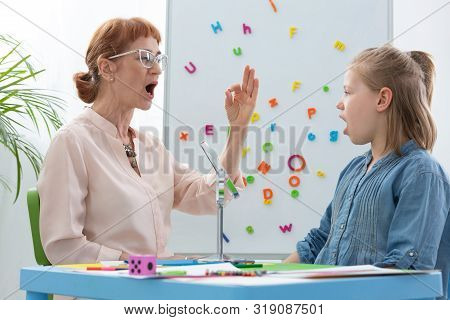 Cute Blond Little Girl Opening Her Mouth During Speech Therapy With Senior Professional Therapist, C