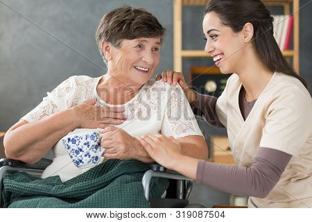 Positive Senior Lady In Wheelchair Holding Cup Of Tea And Smiling To Beautiful Volunteer At Nursing