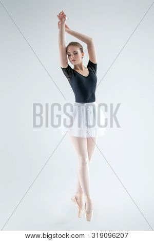 A full length portrait of an elegant ballet female dancer posing in the studio over the white background. Talent, fashion for ballet dancers.