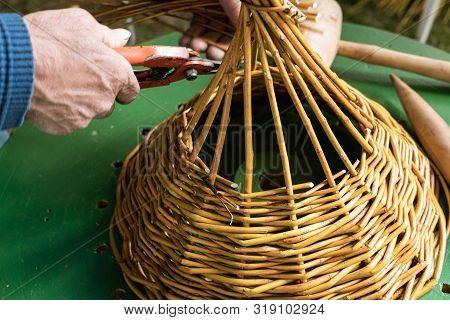 Male Hands Working On Wickerwork Basket. Handcraft Concept