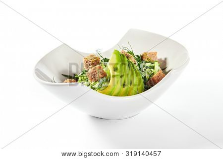Green salad with avocado, cucumber and croutons in white bowl isolated. Healthy exquisite serving vegan salat with sliced alligator pear or avocado pear in restaurant plate closeup poster