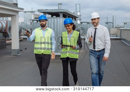 Two Architects Men And Their Assistance African Woman Analyzing The Plan Of Construction Site Walkin