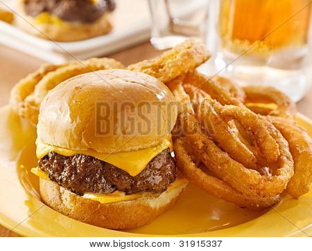mini burgers with cheese and onion rings served with beer.