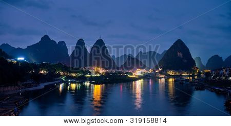 Panorama of Yangshuo town illuminated in the evening with dramatic karst mountain landscape in background over Li river. Yangshuo, China