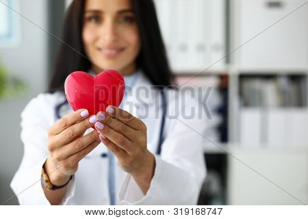 Female Cardiolog Holding In Arms Red Toy Heart Closeup. Infarction Protection And Sickness Prophylax