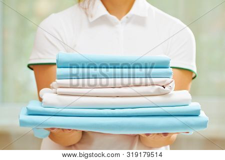 Closeup Of Woman's Hand Holding A Stack Of Clean Folded Bed Sheets Of Blue And White Colors. Blurred