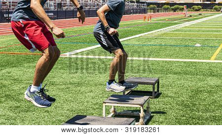 Two Male High School Track And Field Athletes Doing Box Jumps On A Green Turf Field During Strength