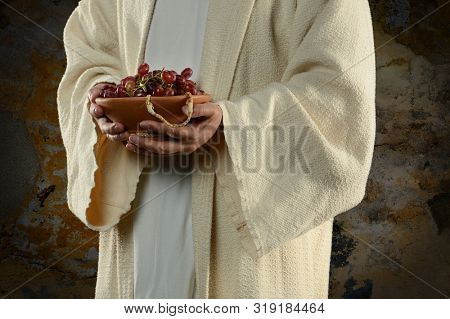 Hands of Jesus Holding bowl with grapes symbolizing the wine